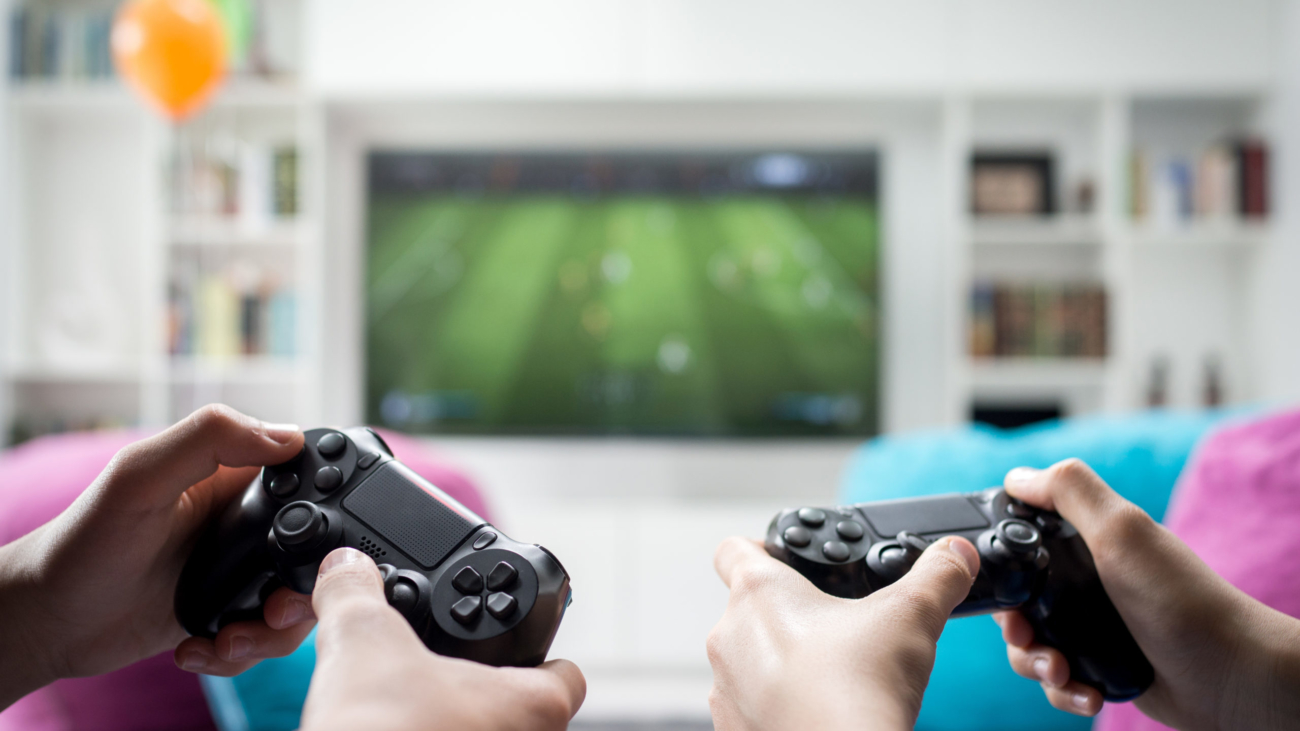 Two boys sitting at home playing video games on game console